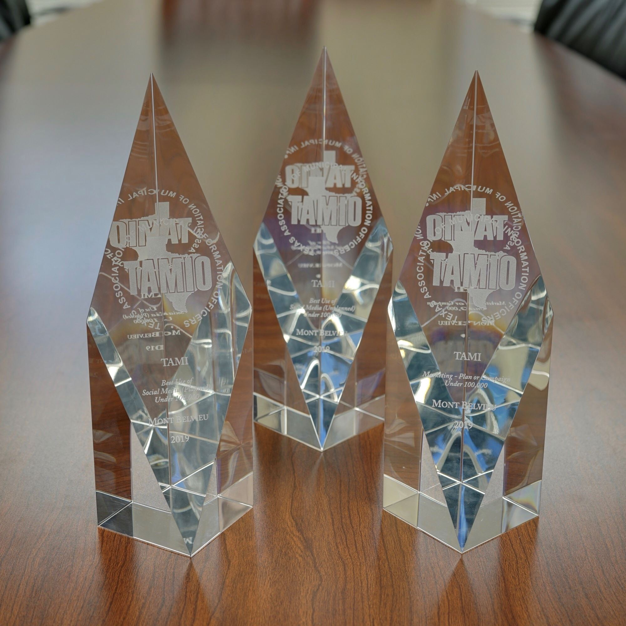 Three clear glass TAMI Awards sit on a table